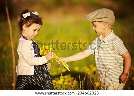 boy and girl in summer field - stock photo