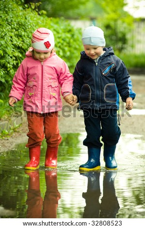 boy and girl in the puddle - stock photo