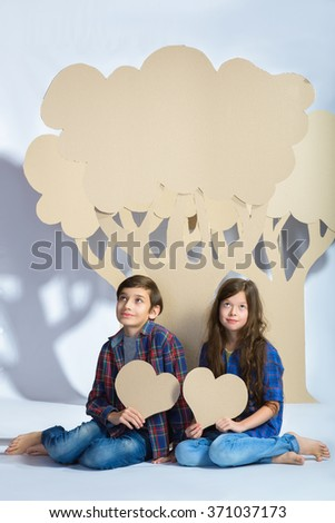 boy and girl keep hearts sit under cardboard tree. Love concept - stock photo
