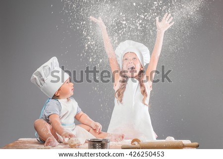 Boy and girl kneading the dough from flour, which comes from the top and is scattered on the table. Sister and brother having fun in the kitchen. - stock photo