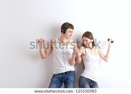 boy and girl  listening of a music and dancing on wall background - stock photo