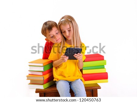 Boy and girl looking at e-book surrounded by several books, isolated on white background - stock photo