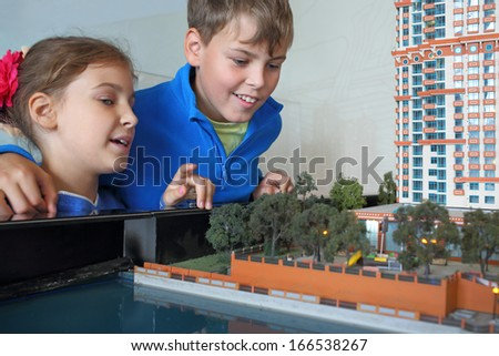 Boy and girl looking at the layout of the area with housing, focus on the boy. - stock photo