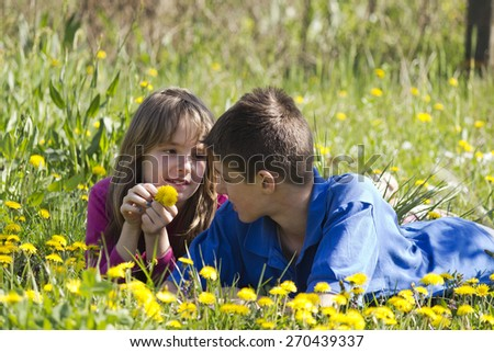 Boy and girl lying in a field of dandelion - stock photo