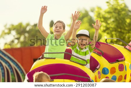 Boy and Girl on a thrilling roller coaster ride at an amusement park with arms raised and yelling with excitement  - stock photo