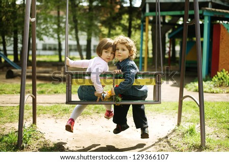 boy and girl on the swings on playground - stock photo
