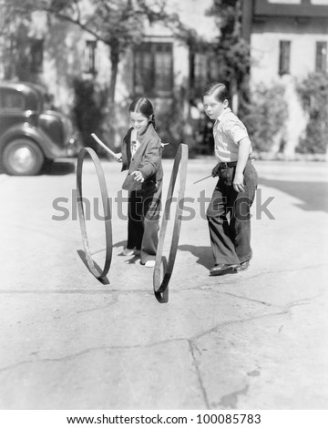 Boy and girl playing hoop and stick on a sidewalk - stock photo