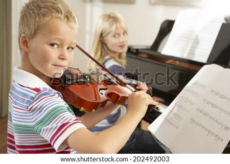 Boy and girl playing violin and piano at home - stock photo
