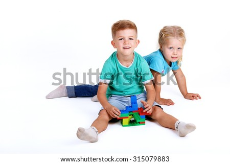 boy and girl playing with plastic blocks on white background - stock photo