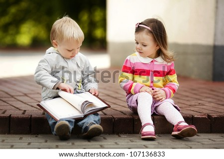 boy and girl reading book - stock photo