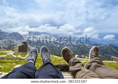 Boy and girl relaxing under the sun.Man and woman lying on sunbed and looking at beautiful background,snow mountains and clouds.Happy couple are outdoor on vacation.Two pairs of male and female's feet - stock photo