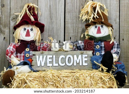 Boy and girl scarecrows sitting on straw bale holding rustic wood welcome sign - stock photo