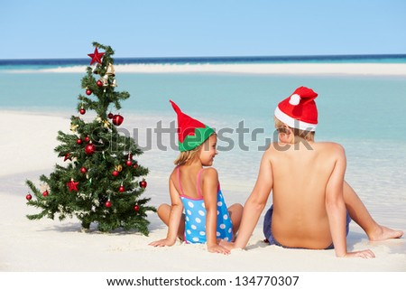 Boy And Girl Sitting On Beach With Christmas Tree And Hat - stock photo