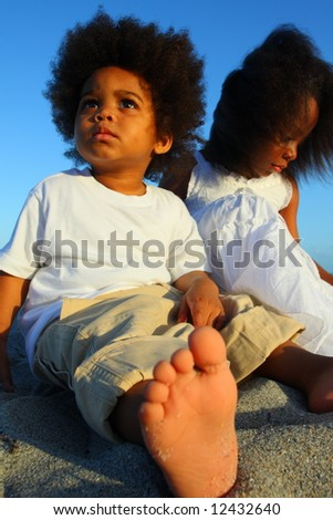 Boy and girl sitting on the sand - stock photo