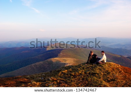 Boy and girl sitting on top of the mountain and are kept in hand. Spring landscape with a couple in love in the mountains - stock photo