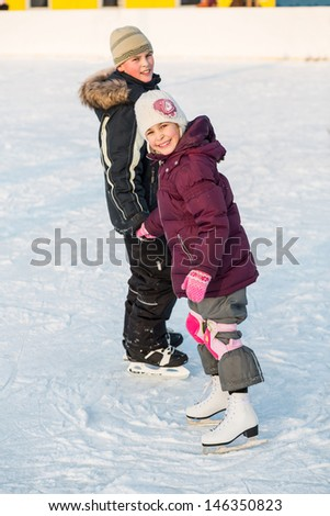 Boy and girl skating on rink hand in hand in winter, focus on a girl - stock photo