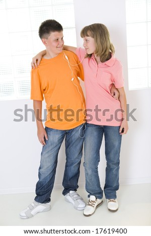 Boy and girl standing in front of window and listening to music by earphones. They smiling and looking each other. - stock photo