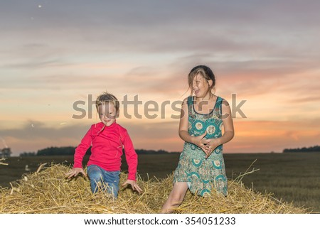 Boy and girl standing on a stack of straw yellow, jump and throw her up against the setting, the rising sun in the clouds - stock photo