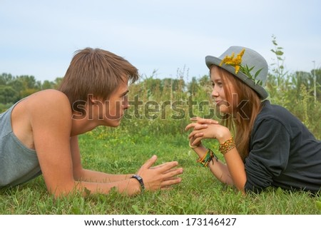 Boy and girl, teenagers lying on the grass and looking into each others eyes - stock photo
