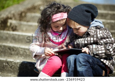 boy and girl using tablet together - stock photo