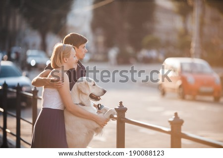Boy and girl watching sunset with dog - stock photo