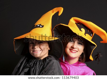 Boy and girl wearing halloween costume  on black background - stock photo