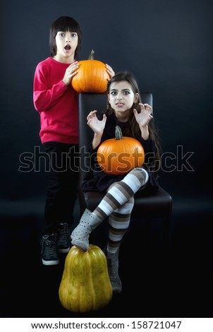 Boy and girl wearing halloween costume with pumpkin on black  background - stock photo