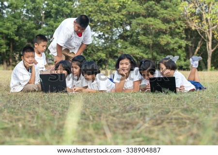 boy and girl with notebook on the grass - stock photo