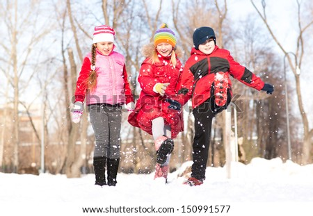 Boy and girls playing with snow in winter park, spending time together outdoors - stock photo
