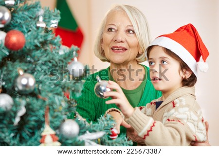 Boy and grandma hanging together christmas tree balls on a tree - stock photo