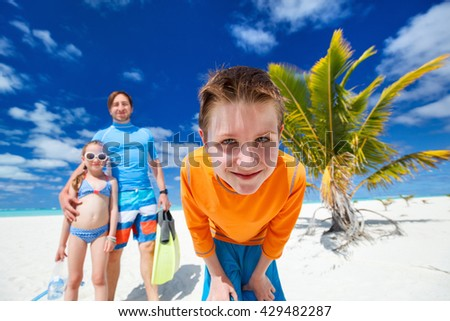 Boy and his family with snorkeling equipment enjoying beach vacation - stock photo