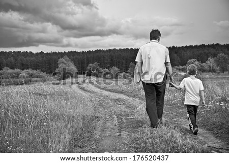 boy and his father are on the road away - stock photo