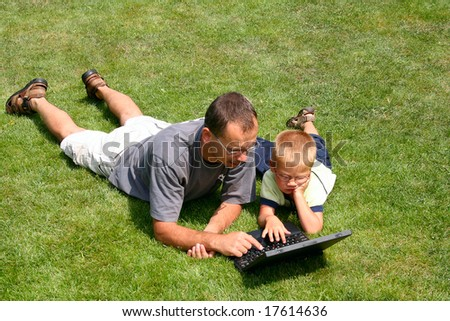 boy and his father's working on laptops on grass - stock photo