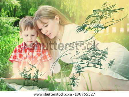 Boy and his Mother Reading a fairy tales with heroes of legends, sitting on green grass  - stock photo