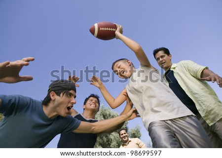 Boy and Men Playing Football - stock photo