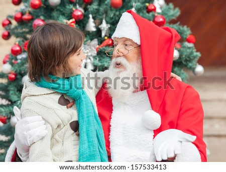 Boy and Santa Claus looking at each other in front of Christmas tree - stock photo