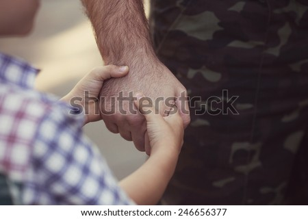 boy and soldier in a military uniform say goodbye before a separation - stock photo