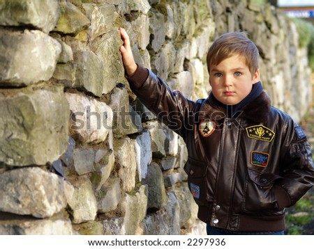boy and stones wall - stock photo