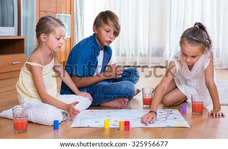 Boy and two little american girls playing at board game indoors - stock photo
