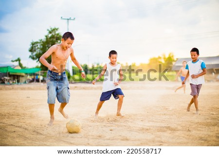 boy are playing football in the sunshine day - stock photo