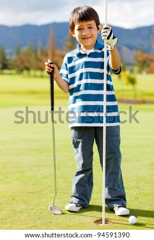 Boy at the course next to a hole playing golf - stock photo