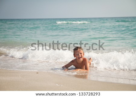 boy at the sea lying in the sand and waves - stock photo