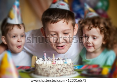 boy blows out the candles on a birthday cake and hugs his brother and sister - stock photo