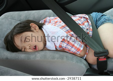 Boy buckle-up seat-belt sleeping in the car - stock photo