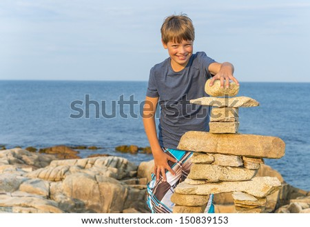 Boy building inukshuk on the rocky beach (Duncan Cove, Nova Scotia, Canada) - stock photo