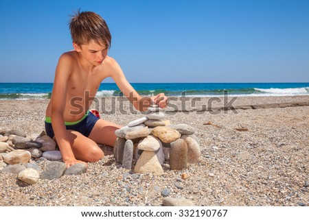 Boy building pebble castle on a beach - stock photo