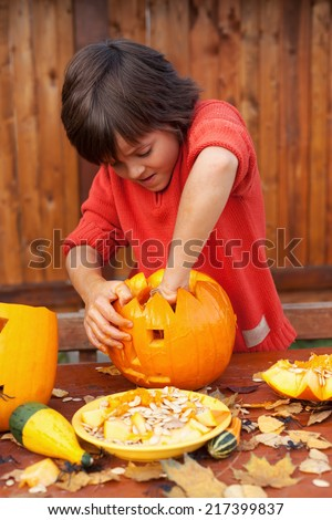 Boy busy carving a pumpkin jack-o-lantern for Halloween - removing the seeds - stock photo