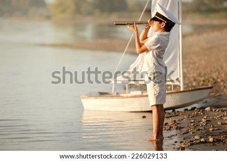 Boy-captain looks into the distance through a telescope at the lake at sunset - stock photo