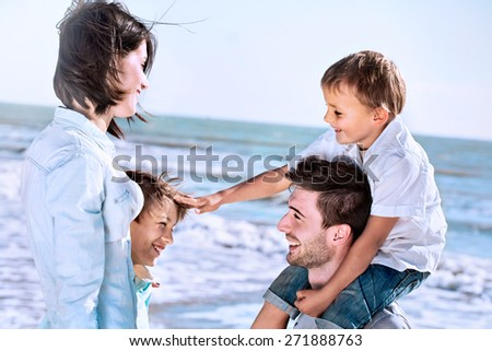 boy caresses his brother with love with his family to the sea - stock photo