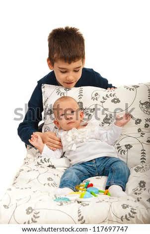Boy caring his little baby sister  against white background - stock photo